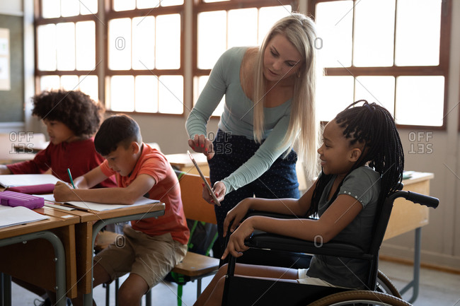Disable mixed race girl sitting in her wheelchair and her female teacher using tablet in the classroom. Primary education social distancing health safety during Covid19 Coronavirus pandemic.