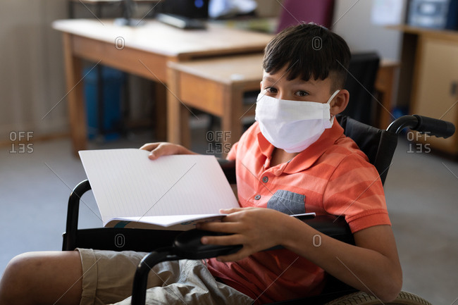 Portrait of disable mixed race boy wearing face mask, sitting in his wheelchair in the classroom. Primary education social distancing health safety during Covid19 Coronavirus pandemic.