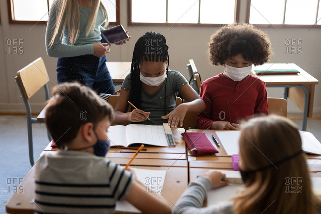 Caucasian female teacher wearing face mask teaching group of multi ethnic kids. Primary education social distancing health safety during Covid19 Coronavirus pandemic.