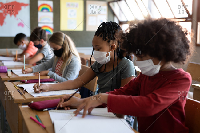 Group of multi ethnic kids wearing face masks while studying in classroom at school. Primary education social distancing health safety during Covid19 Coronavirus pandemic.