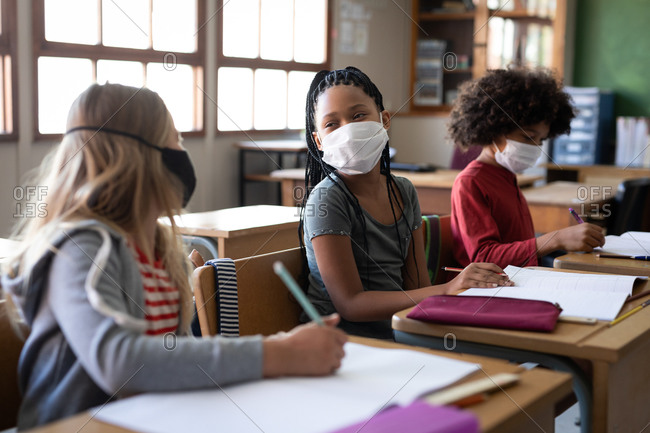 Multi ethnic group of elementary school children sitting at desks wearing face masks in classroom. Primary education social distancing health safety during Covid19 Coronavirus pandemic.