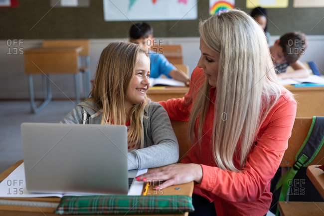 Female Caucasian teacher and a Caucasian girl using laptop during the lesson. Primary education social distancing health safety during Covid19 Coronavirus pandemic.