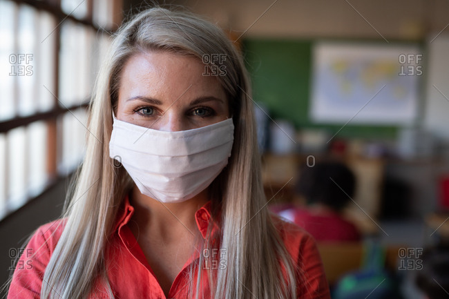 Portrait of a female Caucasian teacher wearing face mask in classroom. Primary education social distancing health safety during Covid19 Coronavirus pandemic.