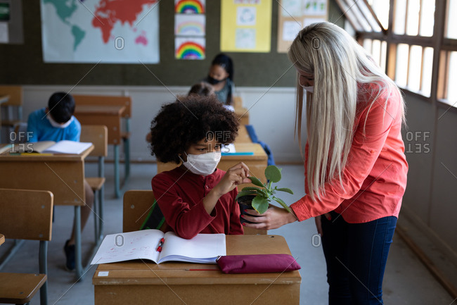 Female Caucasian teacher wearing face mask showing a plant pot to a mixed race boy in school. Primary education social distancing health safety during Covid19 Coronavirus pandemic.