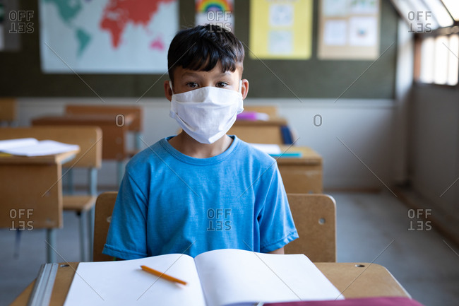 Mixed race boy wearing face mask sitting on his desk at school. Primary education social distancing health safety during Covid19 Coronavirus pandemic.