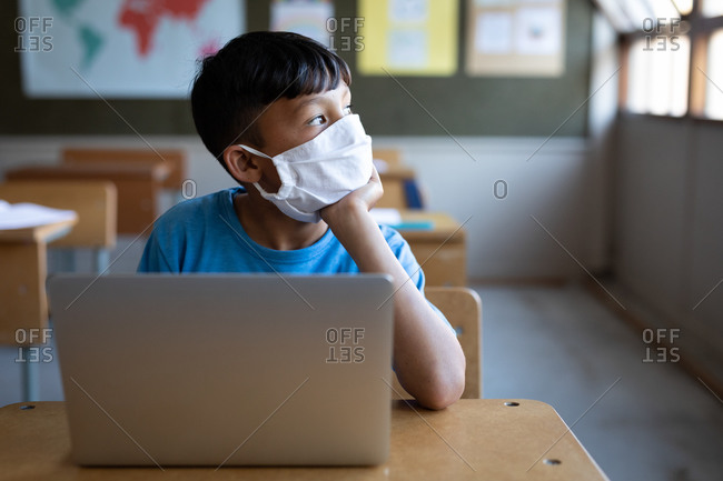 Mixed race boy wearing face mask sitting on his desk at school, using a laptop computer. Primary education social distancing health safety during Covid19 Coronavirus pandemic.