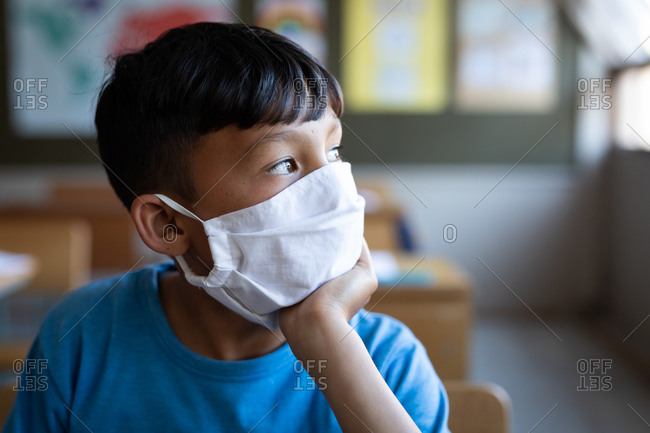 Thoughtful mixed race boy wearing face mask sitting on his desk at school. Primary education social distancing health safety during Covid19 Coronavirus pandemic.