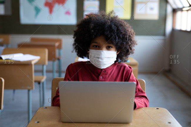 Mixed race boy wearing a face mask, using laptop while sitting on his desk in class at school. Primary education social distancing health safety during Covid19 Coronavirus pandemic.