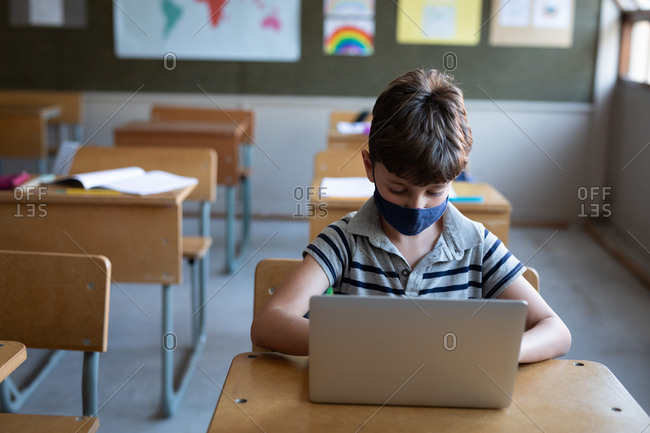 Caucasian boy wearing a face mask, using laptop while sitting on his desk in class at school. Primary education social distancing health safety during Covid19 Coronavirus pandemic.