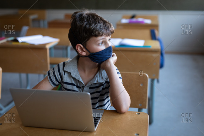 Thoughtful Caucasian boy wearing a face mask, using laptop while sitting on his desk in class at school. Primary education social distancing health safety during Covid19 Coronavirus pandemic.