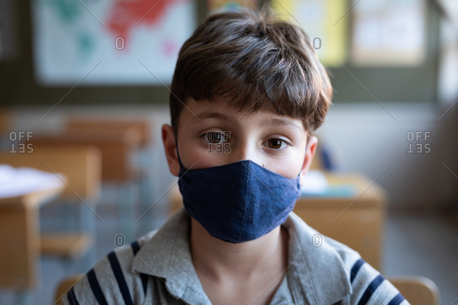 Portrait of a Caucasian boy wearing a face mask, sitting on his desk in class at school. Primary education social distancing health safety during Covid19 Coronavirus pandemic.