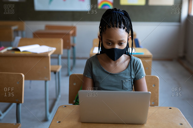 Mixed race girl wearing a face mask, using laptop while sitting on his desk in class at school. Primary education social distancing health safety during Covid19 Coronavirus pandemic.