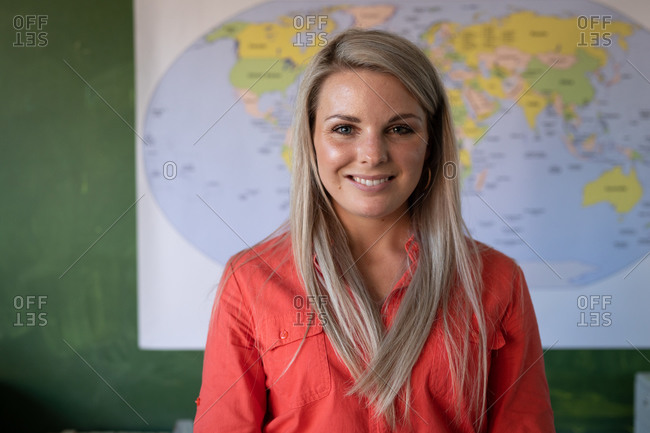 Portrait of a Caucasian female teacher with blonde hair standing in an elementary school classroom. Primary education social distancing health safety during Covid19 Coronavirus pandemic.