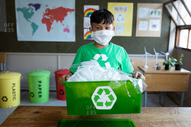 Portrait of a mixed race boy wearing face mask holding a recycle container in class at school. Primary education social distancing health safety during Covid19 Coronavirus pandemic.