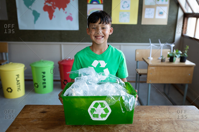 Portrait of a mixed race boy holding a recycle container in class at school. Primary education social distancing health safety during Covid19 Coronavirus pandemic.