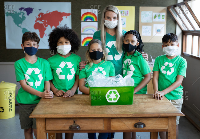 Portrait of female Caucasian teacher and group of multi ethnic kids wearing face masks with recycle container at school. Primary education social distancing health safety during Covid19 Coronavirus.