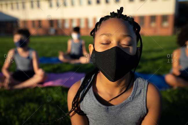 Mixed race girl wearing face mask performing yoga in the school garden. Primary education social distancing health safety during Covid19 Coronavirus pandemic.