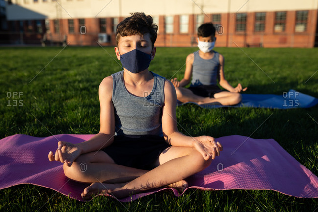 Two multi ethnic boys wearing face masks performing yoga in the school garden. Primary education social distancing health safety during Covid19 Coronavirus pandemic.