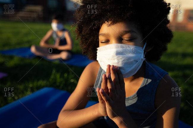 Mixed race boy wearing face mask performing yoga in the school garden. Primary education social distancing health safety during Covid19 Coronavirus pandemic.