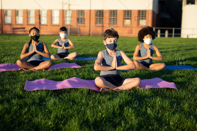 Group of multi ethnic kids wearing face masks performing yoga in the school garden. Primary education social distancing health safety during Covid19 Coronavirus pandemic.