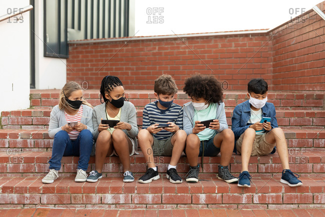 Group of multi ethnic kids wearing face masks using smartphones while sitting on the stairs during a break. Primary education social distancing health safety during Covid19 Coronavirus pandemic.