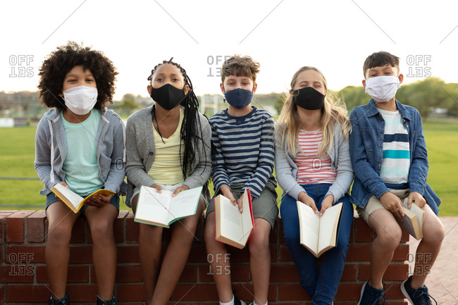 Group of multi ethnic kids wearing face masks reading books while sitting on the wall during a break. Primary education social distancing health safety during Covid19 Coronavirus pandemic.