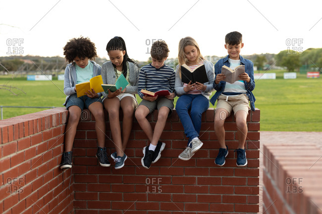Group of multi ethnic kids reading books while sitting on the wall during a break. Primary education social distancing health safety during Covid19 Coronavirus pandemic.