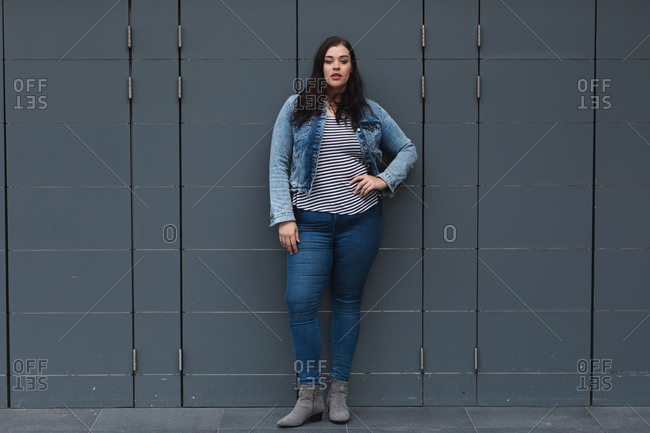 Portrait of Curvy Caucasian woman out and about in the city streets during the day, standing with her hand on hip looking to camera, leaning against a dark grey wall