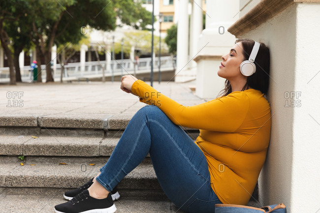 Curvy Caucasian woman out and about in the city streets during the day, sitting on steps, leaning back with eyes closed and listening to music on headphones, with historical building in the background