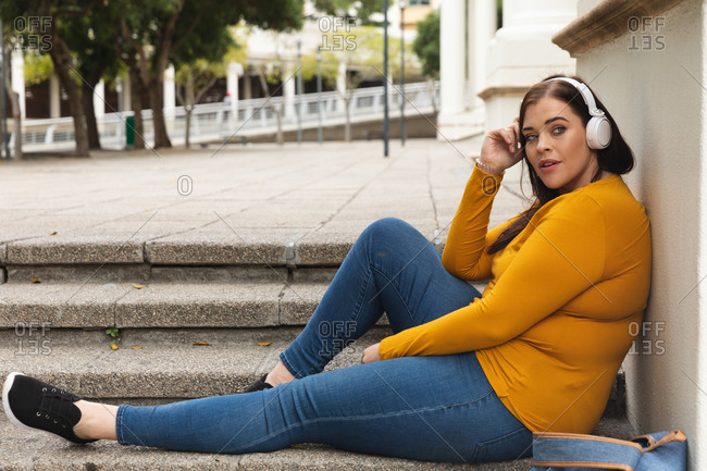Curvy Caucasian woman out and about in the city streets during the day, sitting on steps, leaning back and listening to music on headphones, with historical building in the background