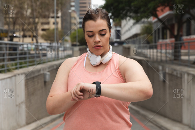 Curvy Caucasian woman with long dark hair wearing sports clothes and headphones exercising in a city, checking her smartwatch, with modern buildings behind her