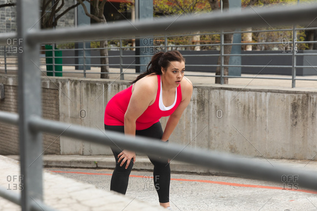 Curvy Caucasian woman with long dark hair wearing sports clothes exercising in a city, leaning forward to take a rest during her work out, with modern buildings in the background