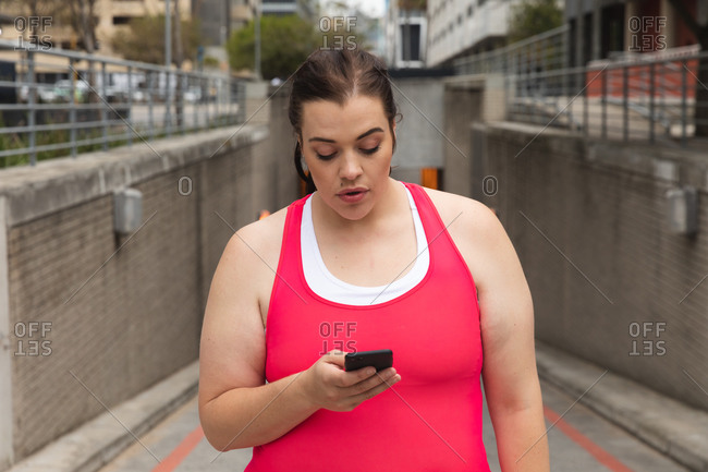Curvy Caucasian woman with long dark hair wearing sports clothes exercising in a city, checking her smartwatch using her smartphone with headphones on with buildings behind her