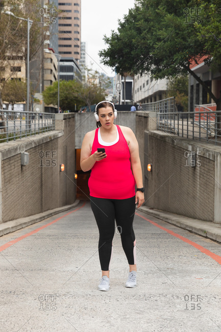 Curvy Caucasian woman with long dark hair wearing sports clothes exercising in a city, using her smartphone with headphones on, with modern buildings in the background