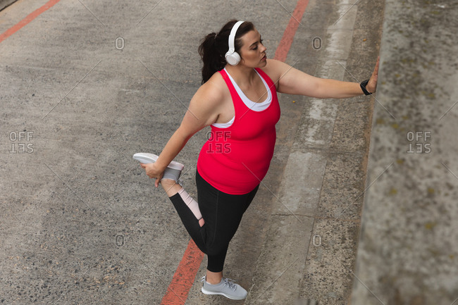 Curvy Caucasian woman with long dark hair wearing sports clothes exercising in a city with headphones on, holding her foot behind her and stretching her leg, leaning against a wall on a walkway