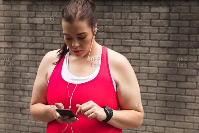 Curvy Caucasian woman with long dark hair wearing sports clothes exercising in a city, using her smartphone with earphones, a brick wall in the background