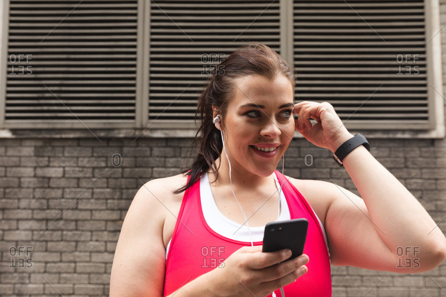 Smiling curvy Caucasian woman with long dark hair wearing sports clothes exercising in a city, using her smartphone with earphones on, a brick wall in the background