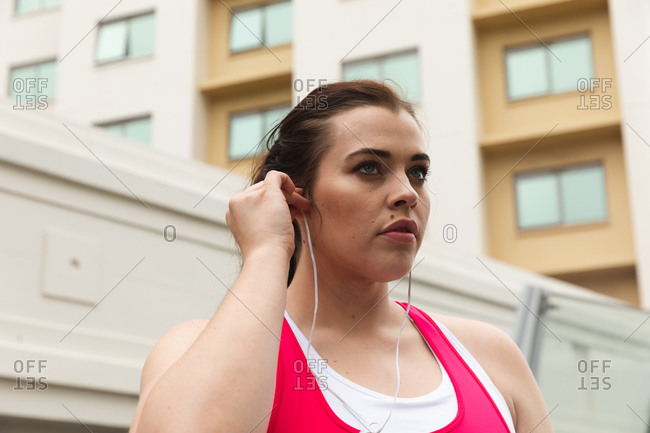 Curvy Caucasian woman with long dark hair wearing sports clothes exercising in a city, putting her earphones on, with modern buildings in the background