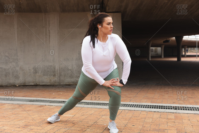 Curvy Caucasian woman with long dark hair wearing sports clothes and earphones exercising in a city, stretching and warming up before her workout