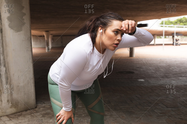 Curvy Caucasian woman with long dark hair wearing sports clothes and earphones exercising in a city, taking a rest and cooling off during her workout