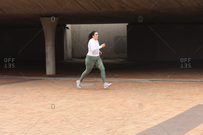 Curvy Caucasian woman with long dark hair wearing sports clothes exercising in a city, running with earphones on in an urban pedestrian area