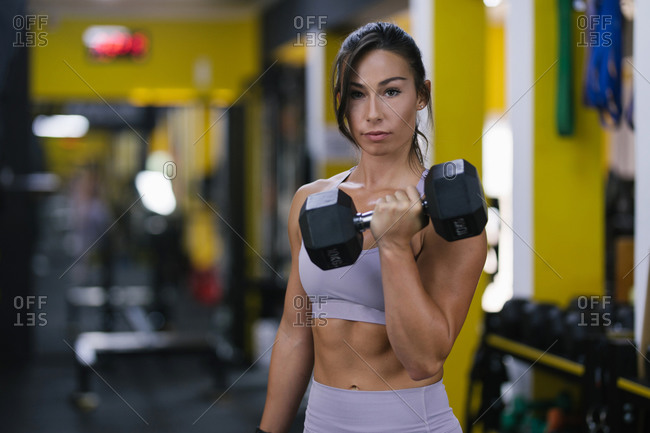 Portrait of strong woman lifting weights