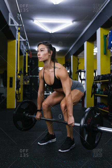 Young woman lifting weight at the gym