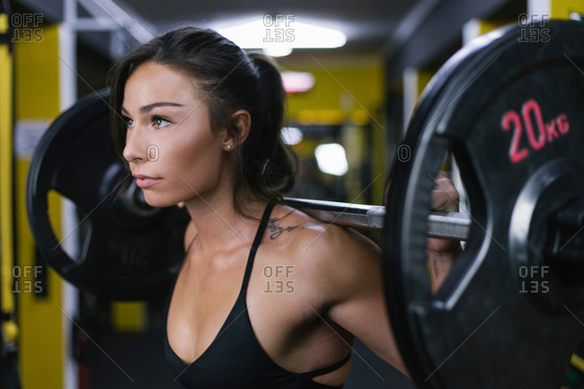 Focused woman lifting weights at gym