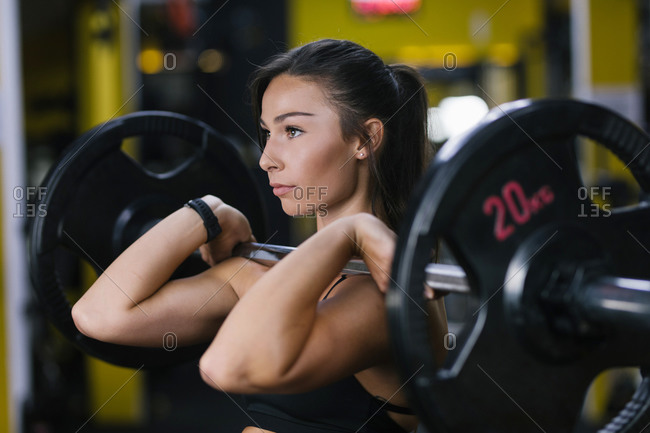 Beautiful young woman lifting weights at gym