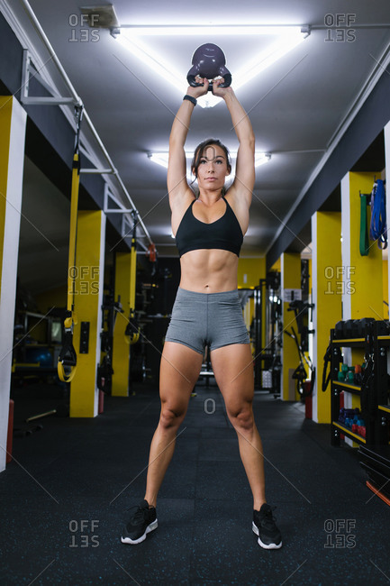Female athlete using kettle bell in gym