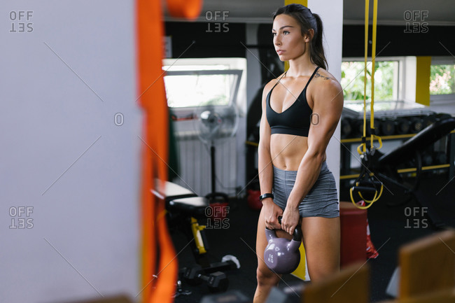 Beautiful young woman working out with kettle bell