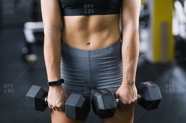Close up of female hands holding dumbbells at gym
