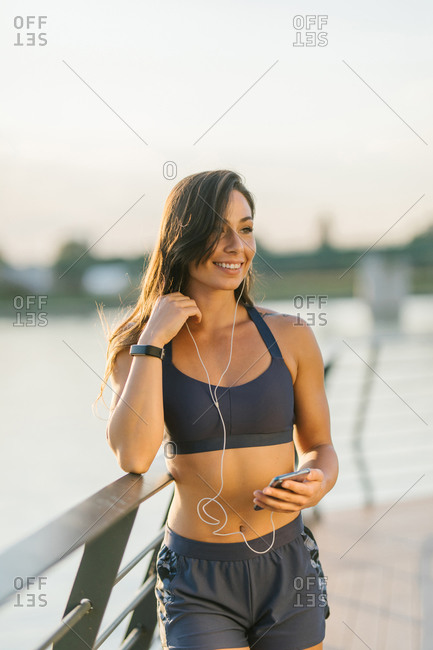 Female athlete making a break and listening the music with headphones