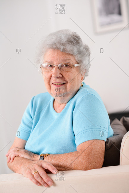 Isolated portrait of a cheerful and dynamic elderly senior woman at home